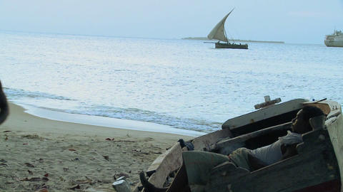 A boy sleeps in a hammock while a dhow sailboat sails by in the distance, Zanzibar Footage