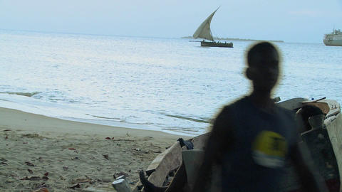 A boy sleeps in a hammock while a dhow sailboat sails by... Stock Video Footage