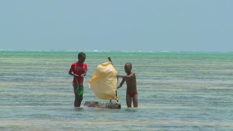 Boys make a crude sailboat in the ocean on a tropical island Stock Video Footage