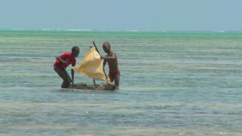 Boys make a crude sailboat in the ocean on a tropical island Footage