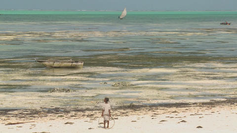 A girl stands with a toy ring on the beach gazing out at a distant sailboat Footage