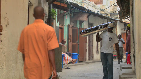 A sunglasses vendor walks on the streets of old Stone Town, Zanzibar Footage