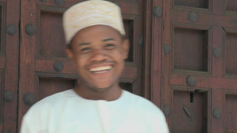 A man smiles and gives a thumbs up to the camera on the streets of Zanzibar Footage