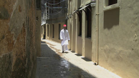 A Muslim man walks in the narrow alleys of Stone Town, Zanzibar Footage