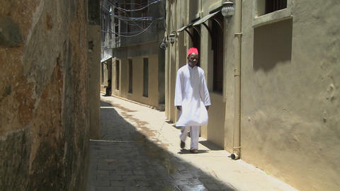 A Muslim man walks in the narrow alleys of Stone Town,... Stock Video Footage