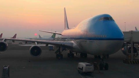 A 747 airplane sits at the boarding gate at sunrise Stock Video Footage
