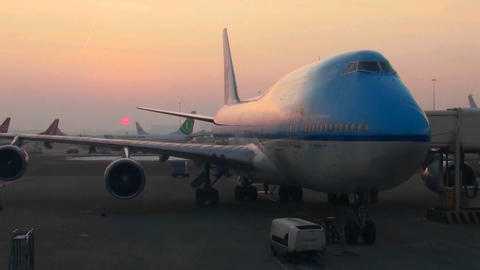 A 747 airplane sits at the boarding gate at sunrise Footage