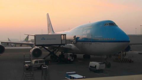 A 747 jet sits at an airport boarding gate at dusk or dawn Stock Video Footage