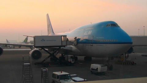 A 747 jet sits at an airport boarding gate at dusk or dawn Footage