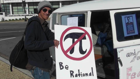 A man holds a sign which says be rational at a campaign rally Footage