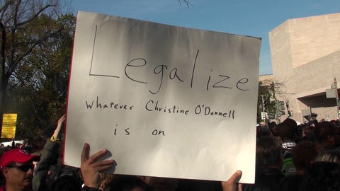A person holds up a sign saying legalize whatever Christine O'Donnell is on at the Jon Stewart rally Footage