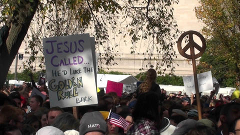 A protestor holds up a sign saying Jesus called and he'd like the golden rule back Footage