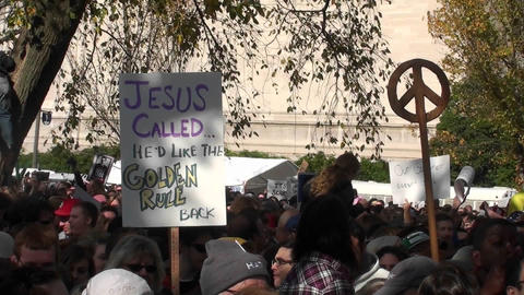 A protestor holds up a sign saying Jesus called and he'd... Stock Video Footage