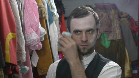 Handsome young male actor applying white face cream for mime make-up Footage