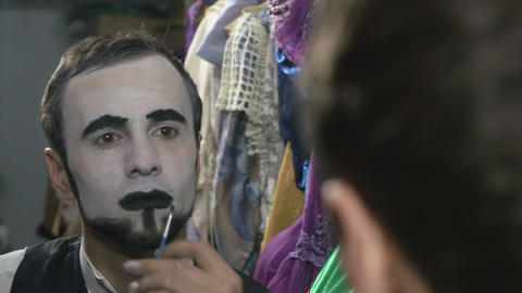 Handsome young man applying black lip stick for mime make-up Footage