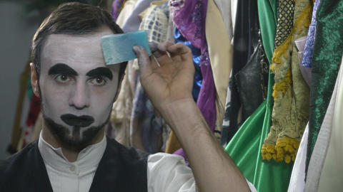Handsome young man applying white face painting for mime make-up Footage