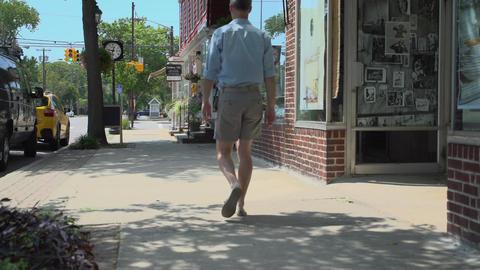 Man strolls down a sidewalk Footage