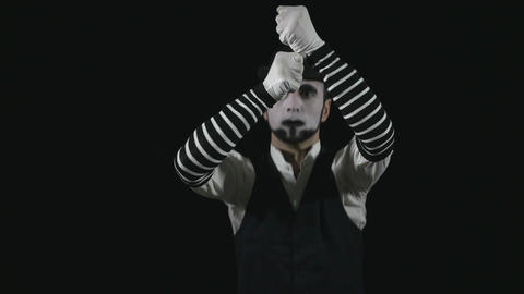 Young funny mime climbing on an invisible rope and falling Footage