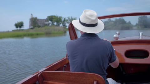 Man driving a classic boat along the coast Footage