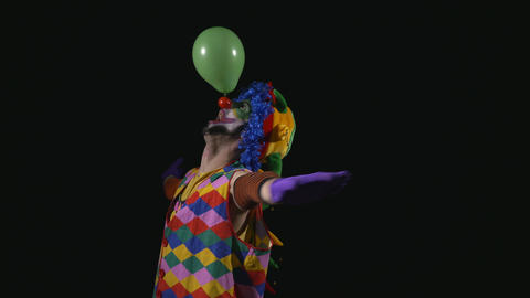 Young funny clown inflating a balloon and balancing it on the nose Footage
