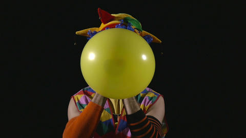 Young funny clown inflating balloon and bursting it Footage