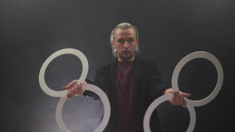 Man wearing a black manipulating with white rings. concentration and Attention Live Action