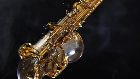 Golden shiny alto saxophone moves on black background with smoke Live Action