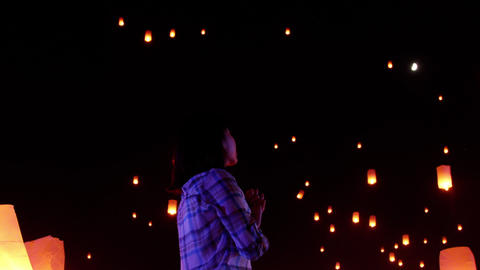 Asian woman watches as sky lanterns fly Into the night sky Live Action