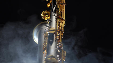 Golden shiny alto saxophone slowly move on black background with smoke Live Action