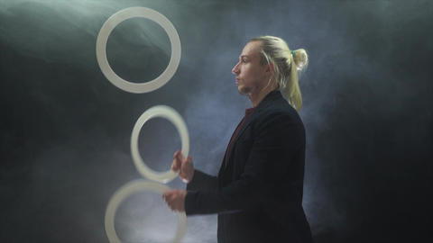 Man wearing a black juggling with white rings. Management, control and success Live Action