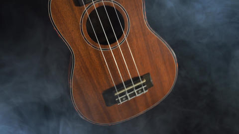 Red wood Hawaii ukulele guitar isolated against black background with smoke Live Action