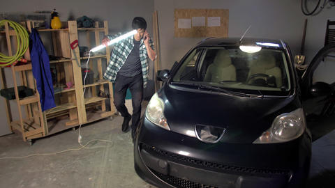 A guy examines a car with a lamp Live Action