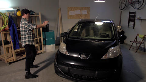 Guy taking pictures of a car in a garage Live Action