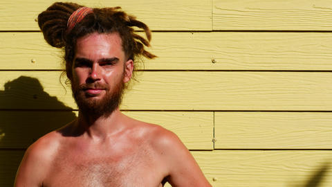 Young dreadful man on a yellow background topless Live Action
