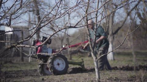 Senior Caucasian man furrowing fertile Ukrainian soil in the early spring Live Action