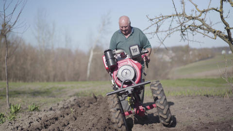 Portrait of serious elderly Caucasian man walking along rural garden with Live Action