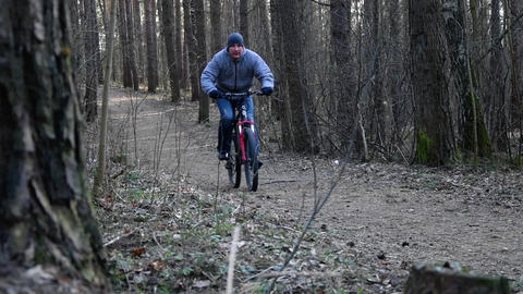 A man rides a Bicycle on a sloping forest road in the spring. Healthy lifestyle, slow motion Live Action