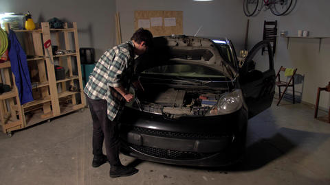 A man repairs a car in a garage Live Action