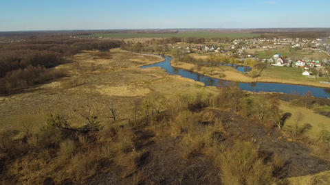 Aerial view of calm rural countryside with river and fields around. Top view of Live Action