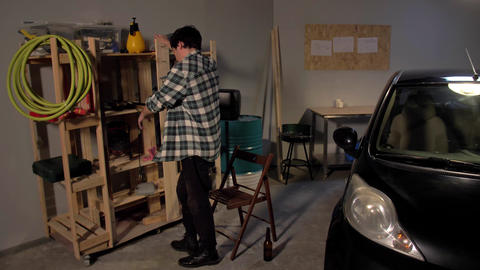 Guy inspects a shelf in garage Live Action
