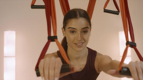 Girl exercising with yoga straps in fitness studio. Woman practicing yoga inside Live Action