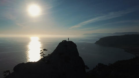 Happy young woman on top of mountain. Aerial view of a silhouette of a young Live Action