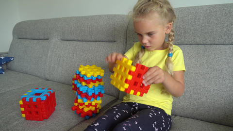 Happy blond female child playing with colorful toys pieces. Gimbal motion Live Action