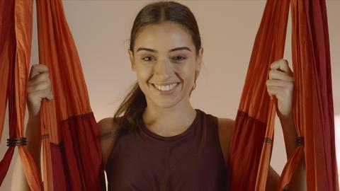 Woman swinging in hammock at yoga studio. Girl sitting in hammock for aero yoga Live Action