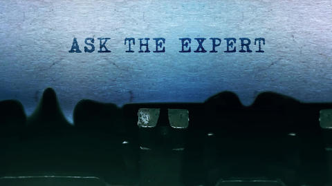 Ask the Expert words Typing on a sheet of paper with an old vintage typewriter Live Action
