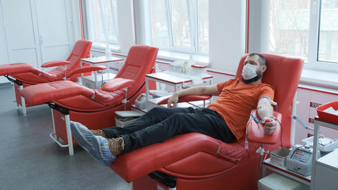 A donor in a mask lies on a couch. Man donates venous blood. Blood donation Live Action