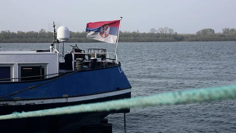 Ship on the river Danube anchored at the docks with Fluttering flag of Serbia. Slow motion 60fps GIF