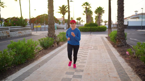 Woman runs down the street along the palm avenue at sunset. Healthy active Live Action
