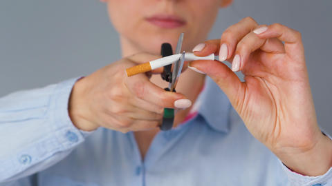 Quit smoking concept, woman cuts cigarette with scissors Live Action