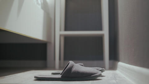 Woman getting out of bed, put on grey slippers Live Action